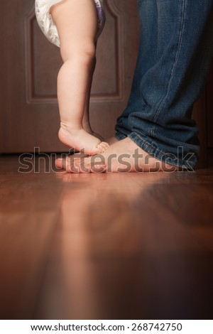 father and baby barefoot on the floor. baby reaches for his father.
