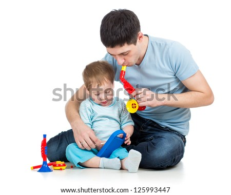 Father and baby boy having fun with musical toys. Isolated on white background