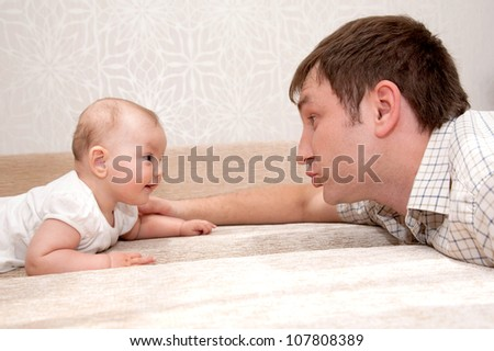 Father and baby daughter, talking, smiling,  lying on the bed and looking eye to eye with each other.