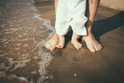 father and baby feet walking on sand beach