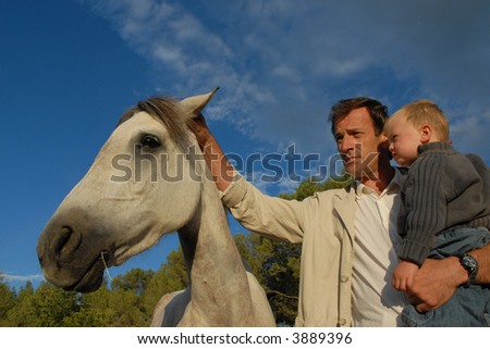 father and baby in an equestrian center