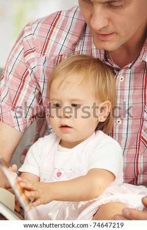 Father and baby sitting together and reading story book.?