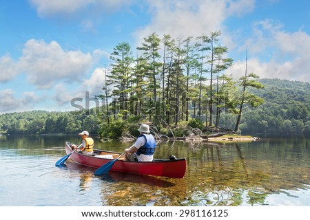 Father and child and the family dog canoeing on a lake on a beautiful, calm summer morning