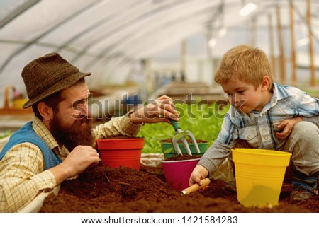 father and child. father and child work in greenhouse. happy family of father and child. father and child at fathers day work in garden. keeping plants hydrated