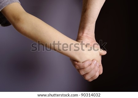 Father and child hands in the dark background