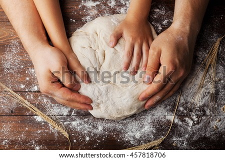 Father and child hands prepares the dough with flour, rolling pin and wheat ears on rustic wooden table from above. Homemade pastry for bread or pizza. Bakery background.