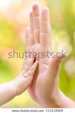 father and child making hi-five gesture