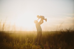Father and child playing at sunset light on field nature