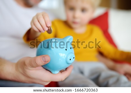 Father and child putting coin into piggy bank. Education of children in financial literacy. Money, cash, investment. Сток-фото ©