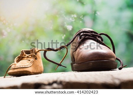 father and child shoes tie the shoestring together in heart shape, love and bound concept