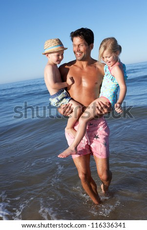 Father And Children Having Fun On Beach