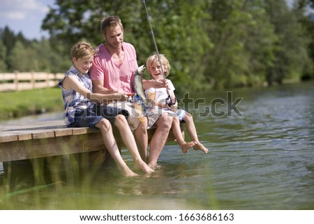 Father and children on jetty fishing