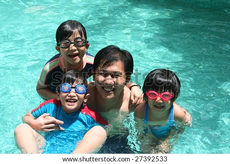 Father and children playing happily in the pool