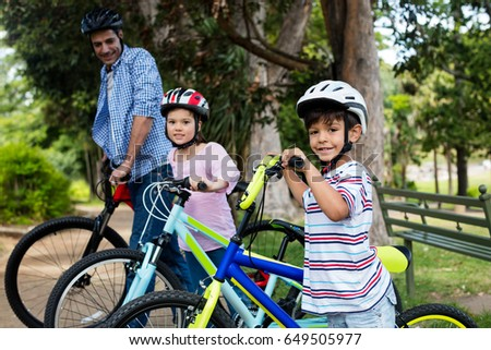 Father and children standing with bicycle in park on a sunny day #649505977
