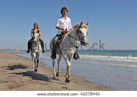 father and daughter are riding with their white horses on the beach
