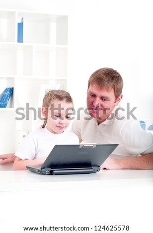 Father and daughter are working together for a laptop at home