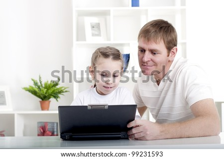 Father and daughter are working together for a laptop at home - stock photo