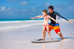 Father and daughter at beach practicing surfing position