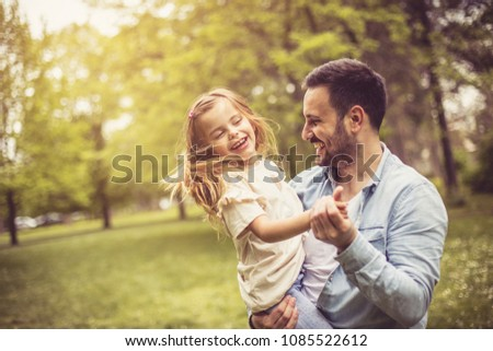 Father and daughter at park dancing and holding hands.
