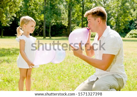 Father and daughter blowing balloons up in park together