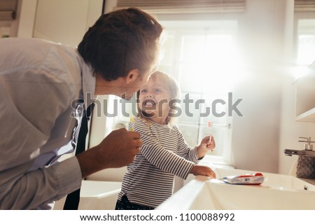 Father and daughter brushing teeth standing in bathroom and looking at each other. Man teaching his daughter how to brush teeth.