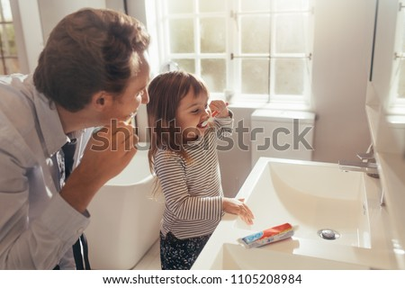 Father and daughter brushing teeth standing in bathroom. Man teaching his daughter how to brush teeth.