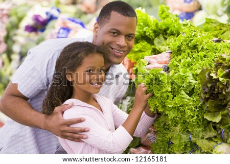 Father and daughter buying fresh produce in supermarket