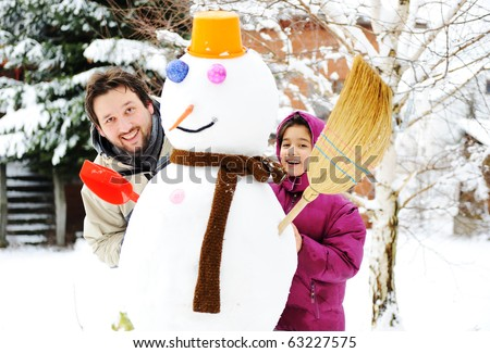Father and daughter, dad and girl playing game with snow-man, winter, december-january