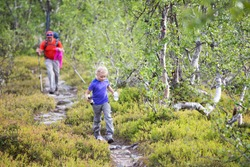 Father and daughter during trekking in Swedish Lapland. The girl runs ahead with bottles of water in her hands. Family vacation.