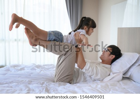 father and daughter enjoy playfull together in house bedroom at comfortable time of holiday weekend #1546409501