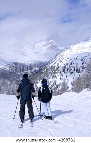 Father and daughter enjoying downhill skiing in winter mountains