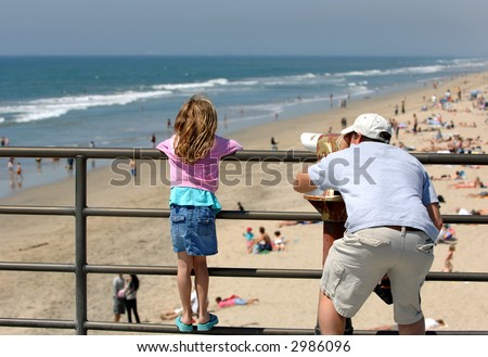 Father and Daughter Examine Coast Through Telescope