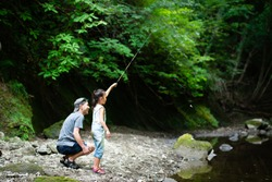 Father and daughter fishing in river