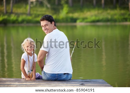 Father and daughter fishing on the lake