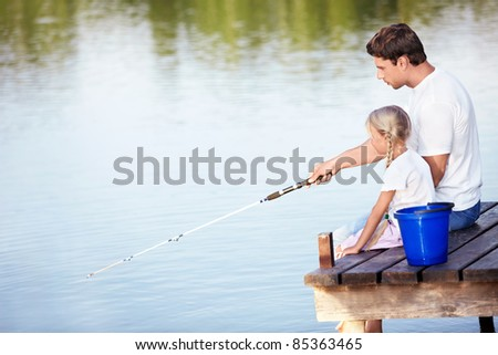 Father and daughter go fishing on the lake