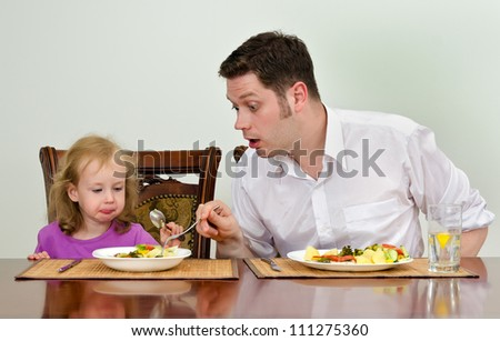 Father and daughter having dinner together in the kitchen