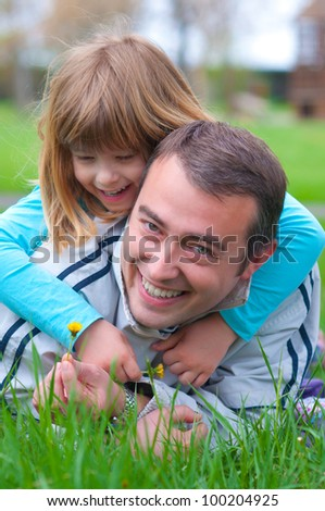Father and daughter having fun in the grass on beautiful spring day.