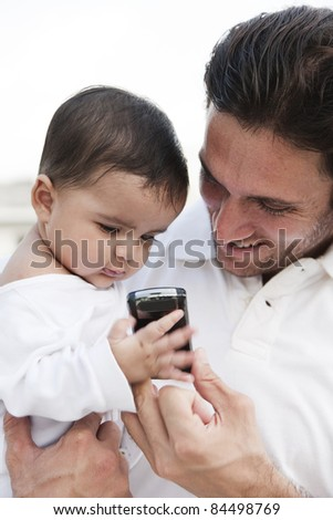 father and daughter holding and looking at the mobile phone.