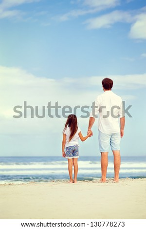 Father and daughter holding hands on the beach together happy and loving vacation