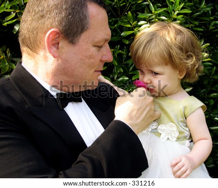 Father and daughter in formal wear smelling roses in outdoor setting