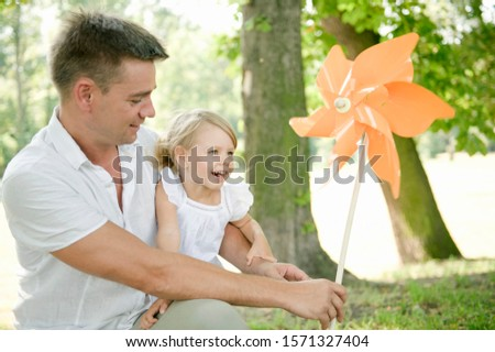 Father and daughter in park with pinwheel