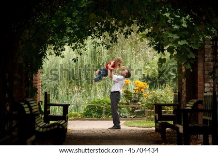 Father and daughter in summer garden  in plant tunnel. Man plays with girl lifting her on hands.