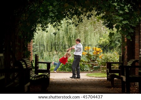 Father and daughter in summer garden  in plant tunnel. Man plays with girl turning her on hands.