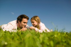 Father and daughter looking at grass