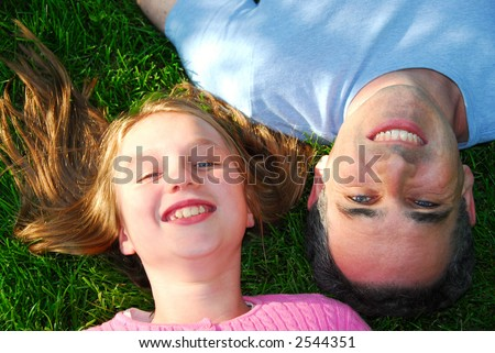 Father and daughter lying on green grass and looking up
