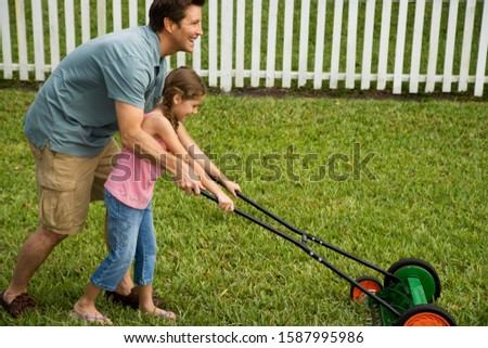 father and daughter mowing the lawn togethern