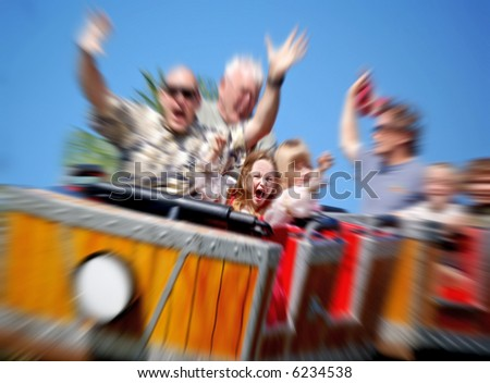 Father and Daughter On Amusement Park Roller Coaster with Zoom Blur