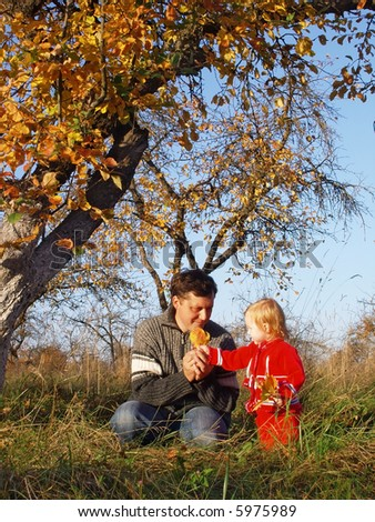 father  and daughter  on background autumn garden - stock photo