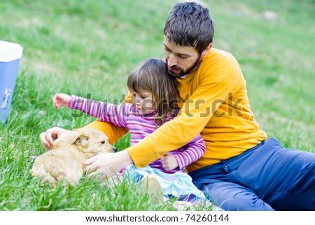 father and daughter on picnic - playing with dog
