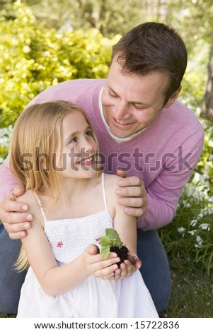 Father and daughter outdoors holding plant smiling